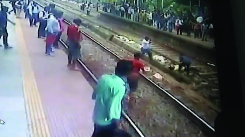 Video grab of the incident; passengers are seen lifting the man from the tracks in order to save him.