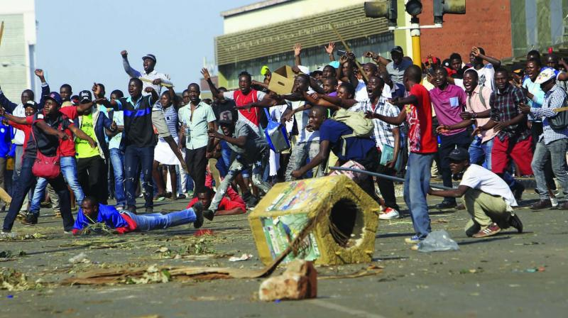 Opposition party supporters react after police fired tear gas, in Harare on Wednesday. (Photo: AP)