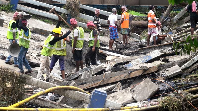 Civic authority personnel clear the debris at the Majherhat Bridge collapse site after DMG personnel declared the rescue operation over. (Photo: Abhijit Mukherjee)