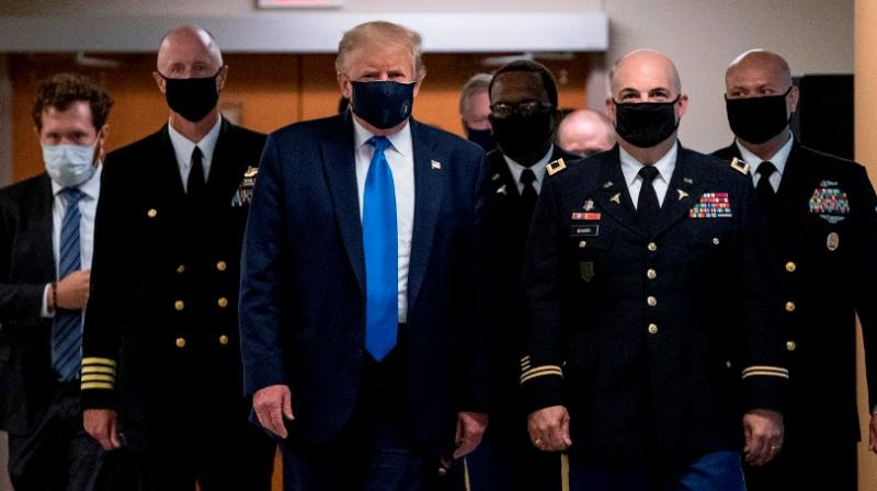 US President Donald Trump wears a mask as he visits Walter Reed National Military Medical Center in Bethesda, Maryland (AFP)