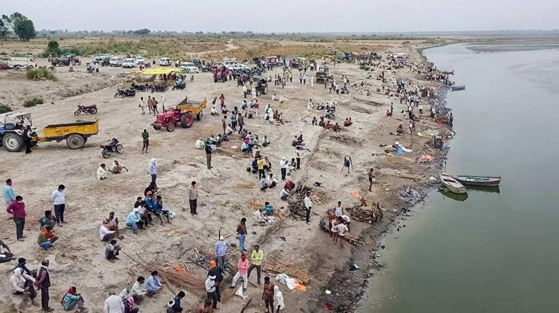 Relatives and family wait to cremate on the banks of River Ganga, in Unnao, Thursday. (Photo: PTI)