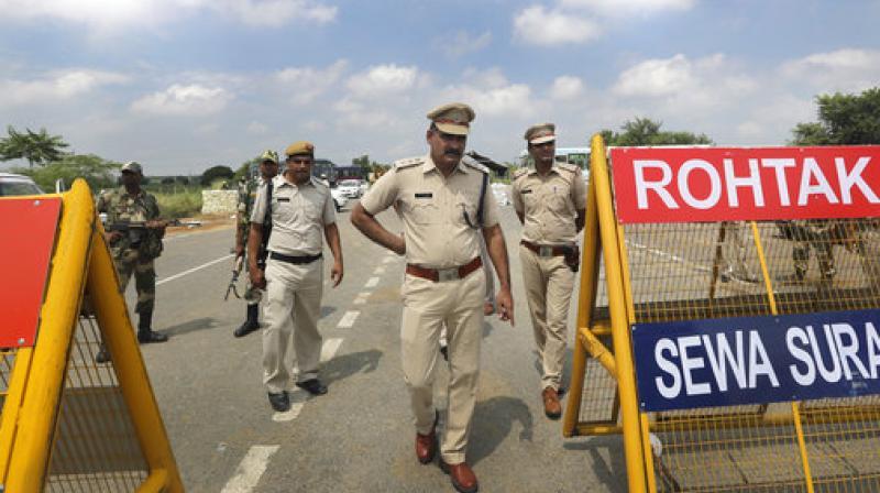 Policemen stand guard at a temporary road blockade near Sunaria Jail where Dera Sacha Sauda sect chief Gurmeet Ram Rahim Singh is being held in Rohtak. (Photo: AP)