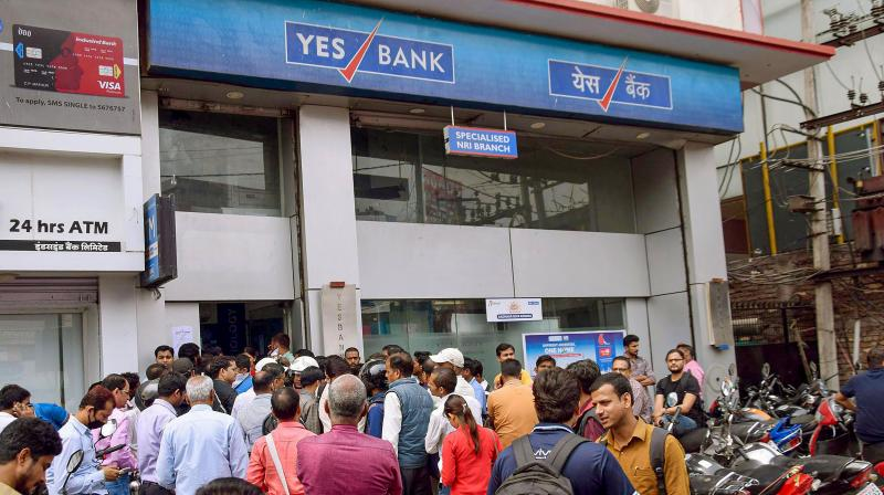 Yes Bank account holders stand outside a branch of the bank to withdraw money in Patna (PTI)
