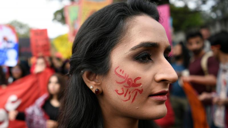 An activist of the Aurat (Woman) March, with a slogan reading freed woman painted in her face attend a rally to mark the International Women's Day in Islamabad (AFP)