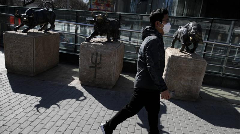 A man wearing a protective face mask walks by statues of bulls on display outside a bank in Beijing (AP)
