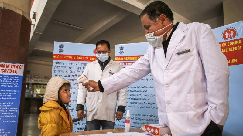 A doctor checks the temperature of a child passenger as part of precautionary measures against the new coronavirus, at a railway station in Jammu (PTI)