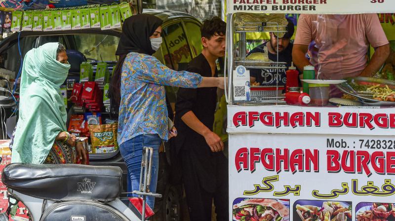 Afghans living in India, purchase food from a street vendor at Lajpat Nagar in New Delhi, Aug. 16, 2021. (PTI/Kamal Kishore)