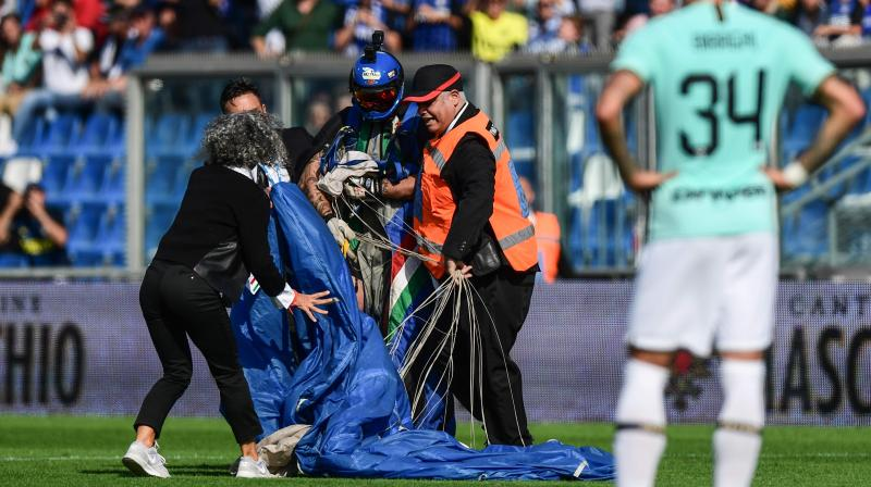 The parachutist was quickly evacuated by security agents at the stadium in Emilia-Romagna. (Photo :AFP)