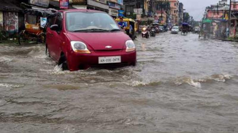 A car wades through a flooded street after heavy downpour in Silchar, Assam, on Thursday. (Photo: PTI)
