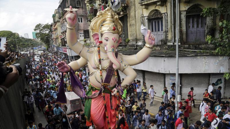 Devotees participate in a procession transporting giant idol of Hindu god Ganesha to a worship venue in preparation of Ganesha Chaturthi festival in Mumbai. (Photo: AP)