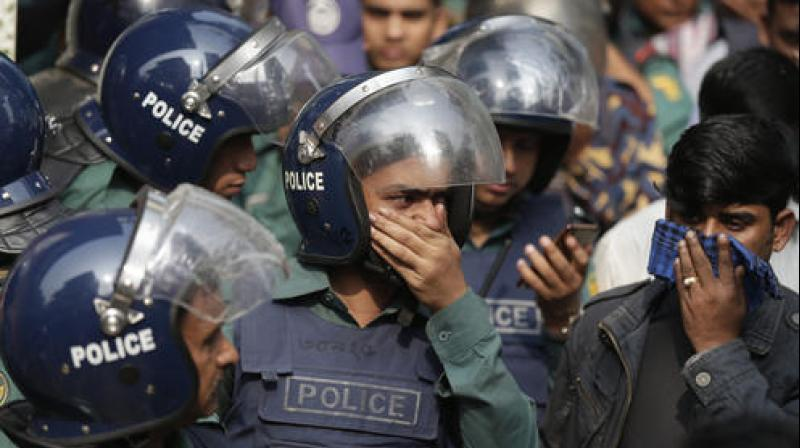 Bangladesh policemen cover their nose to protect themselves from the smell of teargas during a raid in a building in Dhaka. (Photo: AP)