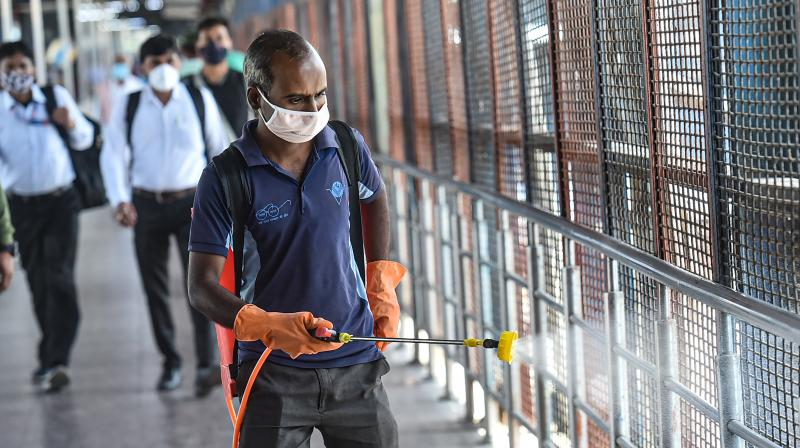 A workers carries out sanitization at New Delhi Railway Station, amid rise in coronavirus cases, in New Delhi. (PTI)