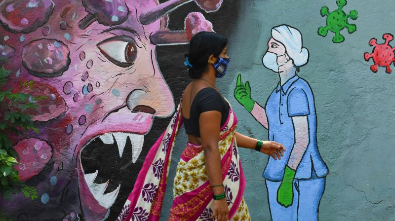 A pedestrian walks past a wall mural depicting a frontline medical staff stopping the Covid-19 coronavirus, in Navi Mumbai on June 7, 2021. (Indranil MUKHERJEE / AFP)