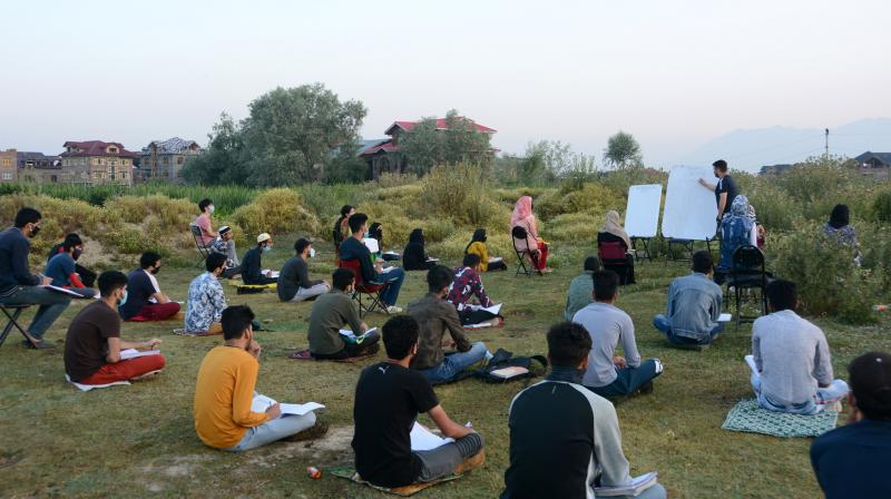 Muneer Aalam hold open-air classes in batches for about eighty students in Srinagar's Idgah grounds.