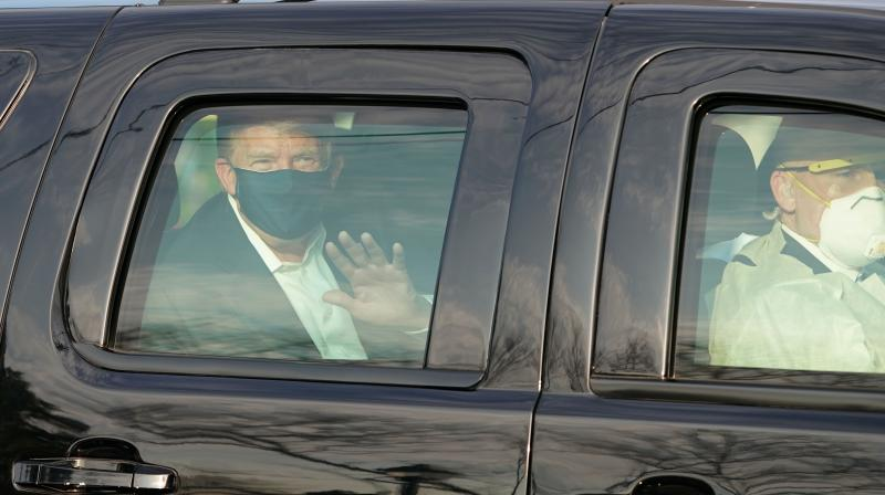US President Trump waves from the back of a car in a motorcade outside of Walter Reed Medical Center in Bethesda, Maryland on October 4, 2020. (AFP)