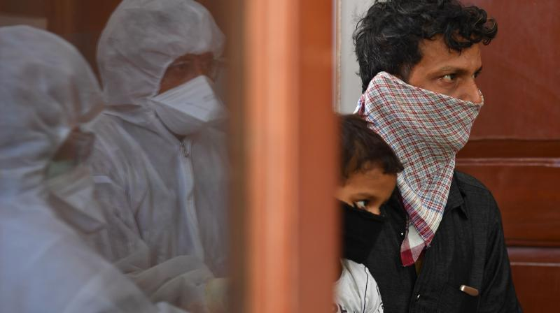 Doctors take the details of a man and a child before testing for Covid19 in Mumbai. (PTI)