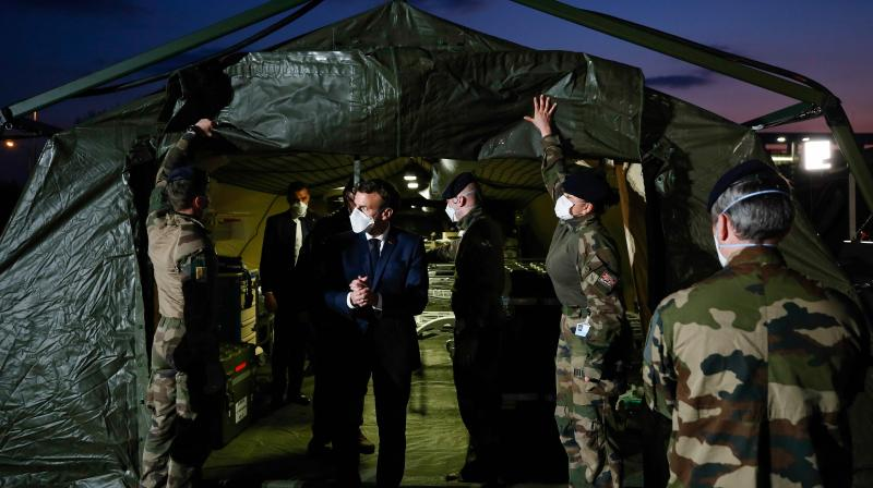 French President Emmanuel Macron (C) wears a face mask during the visit of the military field hospital outside the Emile Muller Hospital in Mulhouse, eastern France. AFP Photo