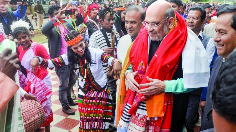 Artists perform as Union home minister Amit Shah arrives to attend the 34th Statehood Day of Arunachal Pradesh, in Lakhimpur Kheri district, Thursday. Assam chief minister Sarbananda Sonowal and Assam finance minister Himanta Biswa Sarma are also seen. (Photo: PTI)