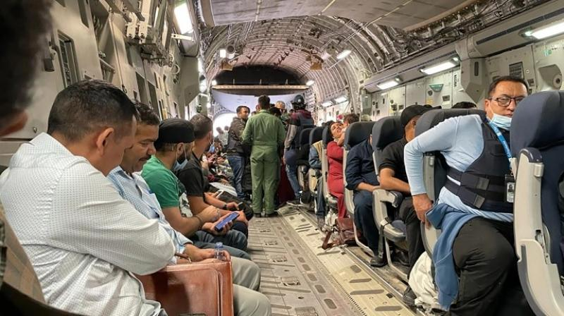 Indian nationals sit on board an Indian military aircraft at the airport in Kabul. (AFP Photo)
