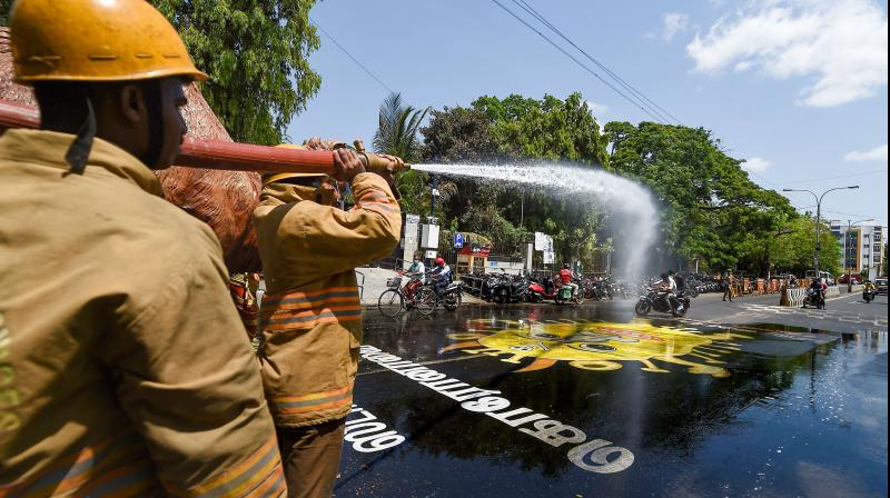 Tamil Nadu Fire and Rescue Services personnel spray disinfectant on a street in Chennai as a preventive measure against the coronavirus pandemic. (PTI)