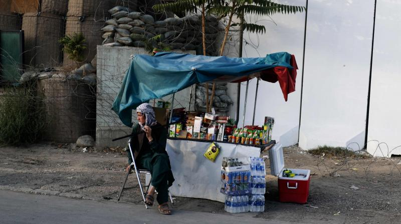 A vendor waits for customers next to his stall along a street in Kabul on September 14, 2021. (Karim SAHIB / AFP)
