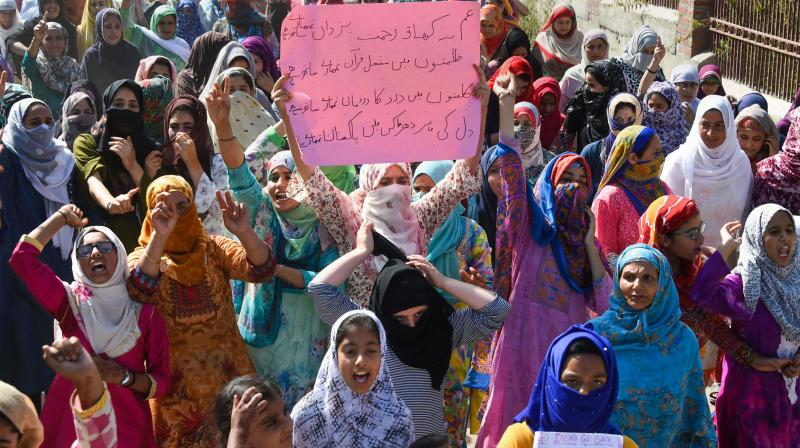 Women hold placards and raise slogans during a peaceful protest march in Srinagar on Friday. (Photo: PTI)