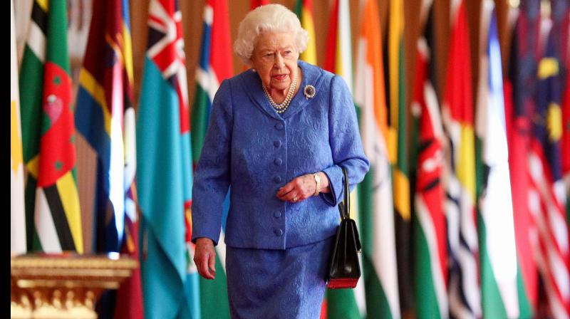 Britain's Queen Elizabeth II walks past Commonwealth flags displayed in St George's Hall at Windsor Castle, Windsor, southeast England on March 5, 2021, to mark Commonwealth Day which is to be celebrated on March 8, 2021. (Steve Parsons / POOL / AFP)