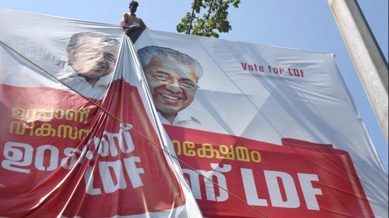 A worker puts up an election campaign banner of Kerala Chief Minister Pinarayi Vijayan, ahead of the Assembly polls, in Kochi on March 5, 2021. (PTI)