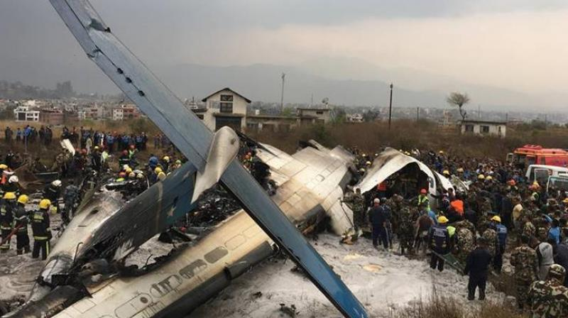 Nepalese rescuers stand near a passenger plane from Bangladesh that crashed at the airport in Kathmandu, Nepal, Monday. (Photo: AP)