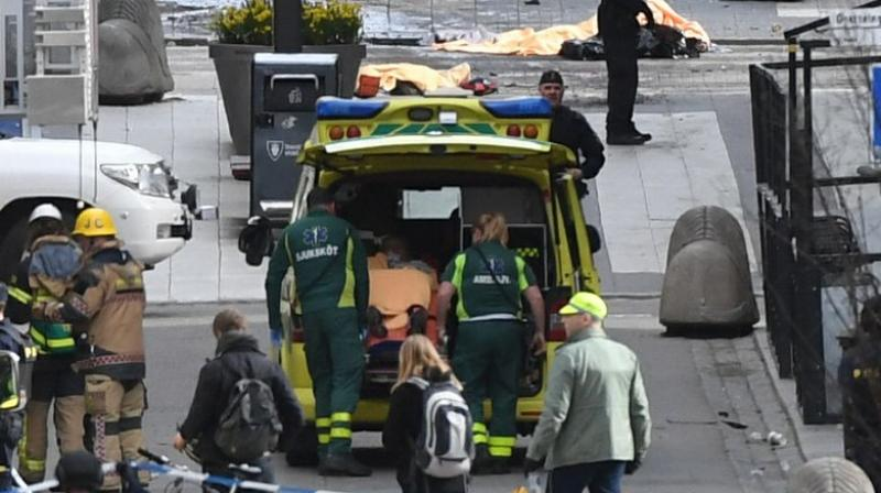 Emergency personnel load a person into an ambulance, centre, at the scene after a truck crashed into a department store injuring several people in central Stockholm, Sweden, (Photo: AP)