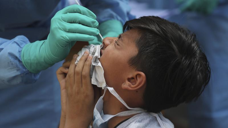 A boy grimaces as a nasal swab is taken to check for Covid-19 infection in Ahmedabad on April 10, 2020. (AP)