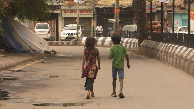 A boy and a girl roam in a deserted street during the current coronavirus lockdown in New Delhi. (DC Photo: Pritam Bandyopadhyay)