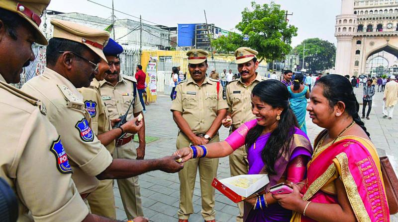Women offer sweet to police personnel as they commend the police in Hyderabad on Friday for its strong action against the four accused in the gangrape and murder of a 25-year-old veterinarian. (Photo: PTI)