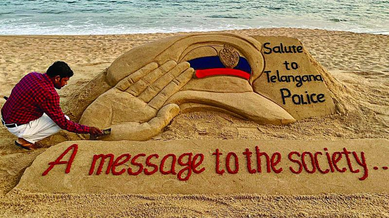 Sand artist Sudarshan Pattnaik creates a sculpture at a beach in Puri to commend the Hyderabad Police for its action against the four gangrape accused on Friday. (Photo: PTI)