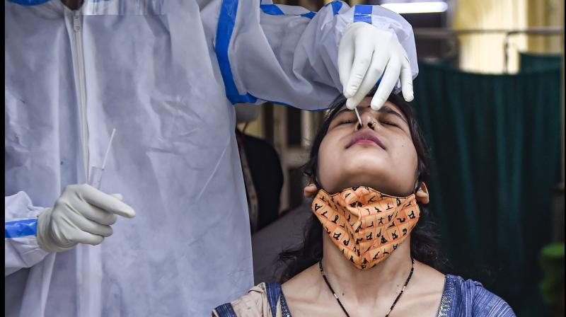 A medic collects swab sample from a woman for COVID-19 tests, at National Institute of TB and Respiratory Diseases, Mehrauli, in New Delhi, Wednesday, May 19, 2021. (PTI/Kamal Singh)