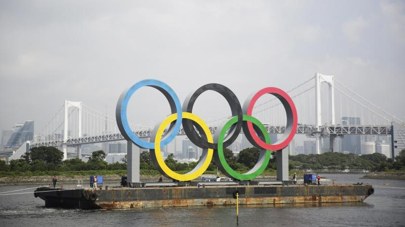 In this Aug. 6, 2020, file photo, the Olympic rings for the Olympic and Paralympic Games Tokyo 2020 pass by on a barge by tugboats off the Odaiba Marine Park in Tokyo. (Photo: AP)