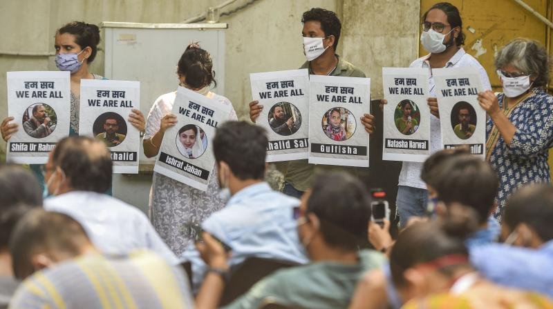 Social activists display placards during a press conference over police probe on Delhi riots cases, at Press Club of India in New Delhi