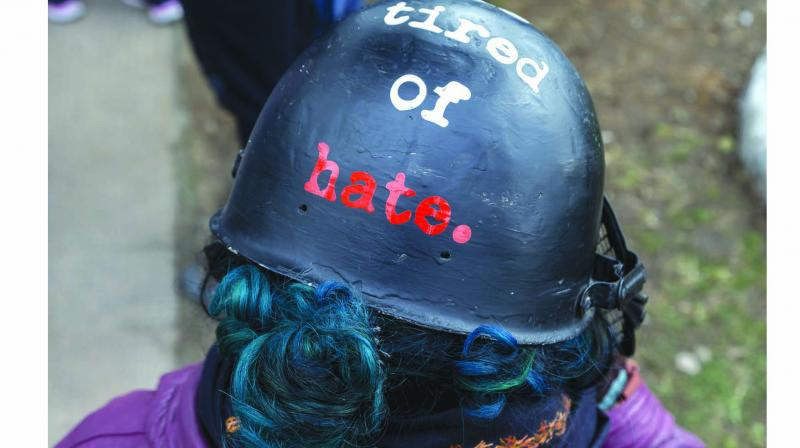 A woman wears a helmet with the words 'The World is Tired of Hate' in Dharmshala on Thursday.