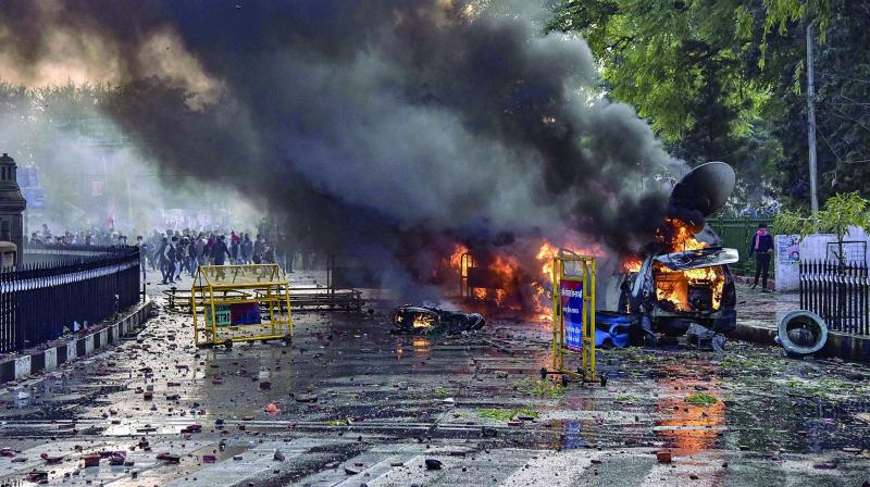 Protesters go berserk in Lucknow. Smoke billows out of a burning media OB van during a protest against NRC and amended Citizenship Act, at Parivartan Chowk in Lucknow on Thursday. (Photo: PTI)