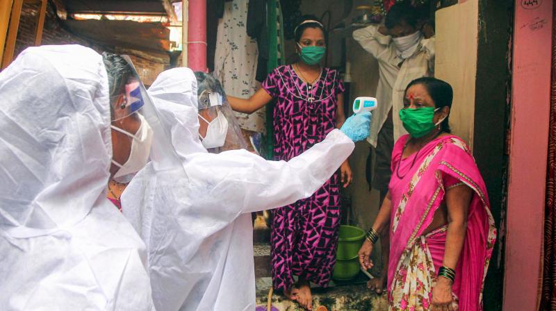 A medic checks the temperature of a woman during door-to-door COVID19 tetsing at Appa Pada slum, Malad, Mumbai. PTI photo