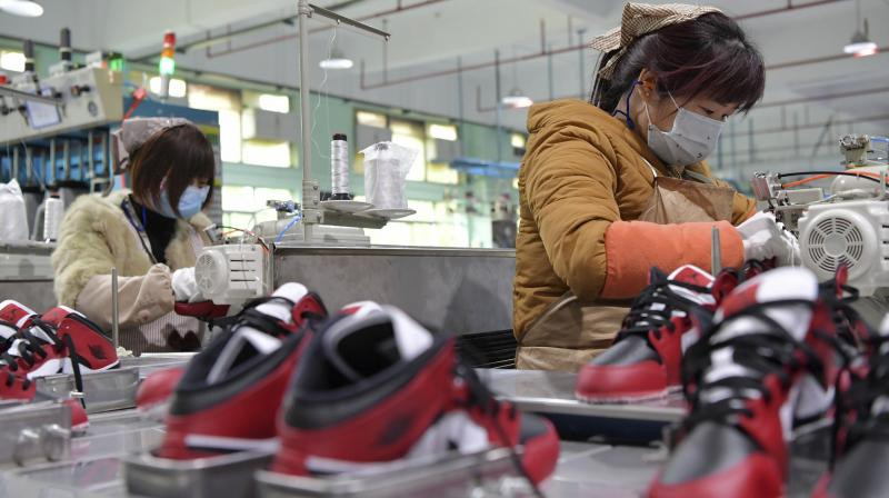 Workers wear masks as they manufacture shoes at a factory in the town of Xiangtang, Nanchang county in eastern China's Jiangxi Province. The ruling Communist Party has told local officials to help reopen factories that were idled by the most intensive anti-disease controls ever imposed. (AP)