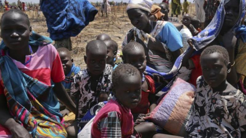 A family waits for food assistance to be distributed in Thonyor, Leer County, one of the areas in which famine has been declared, in South Sudan. (Photo: AP)