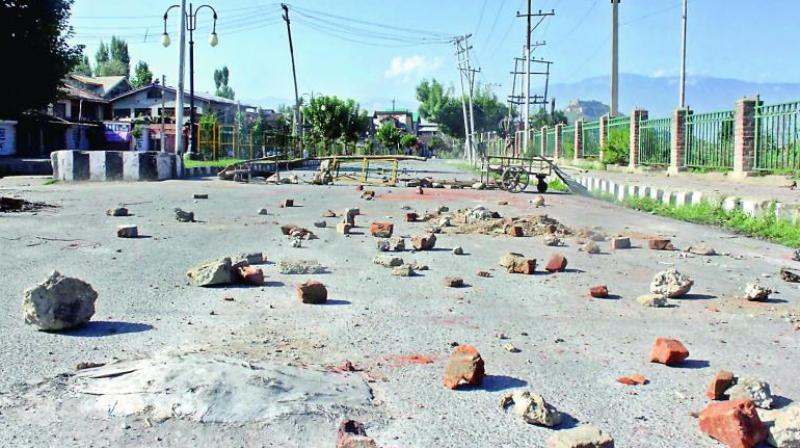 A street in Srinagar wears a deserted look with stones strewn across the road after protests against revocation of Article 370. Central Kashmir DIG Police V.K. Birdi said only minor incidents of violence had occurred in Srinagar on Monday. (Photo: H.U. Naqash)