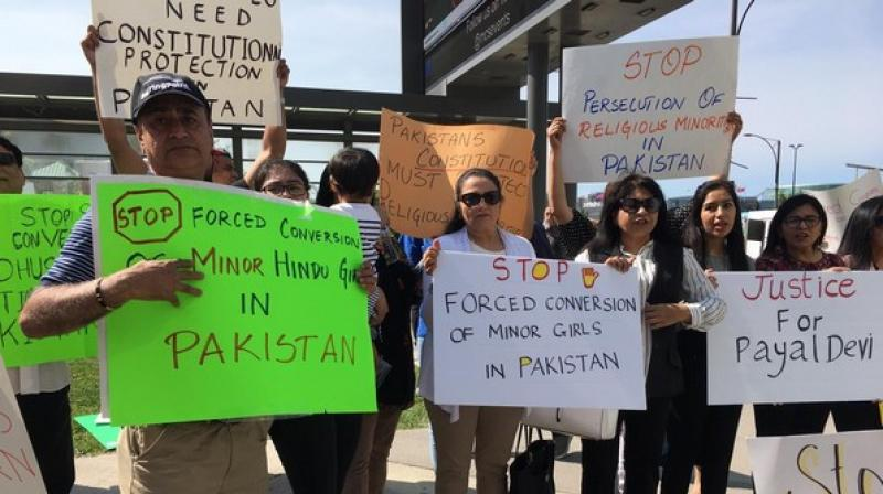 Scores of protesters, mostly Hindus from Sindh who have made Canada their home, on Saturday gathered at the Mississauga Celebration Square here, demanding Pakistan to stop forced religious conversion of minor Hindu girls and justice for those who have been forcibly converted. (Photo: ANI)