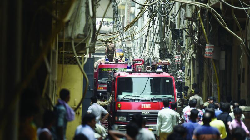 Fire tenders carry out rescue operation at the factory in Shahdara where massive fire broke out on Saturday. A fireman (right) engaged in the rescue operation. (Photo: PTI)