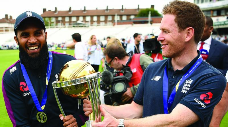 England captain Eoin Morgan and Adil Rashid with the World Cup trophy. (Photo: AFP)