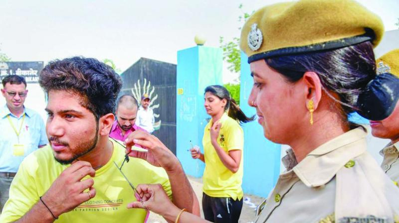 An applicant appearing for a Rajasthan police constable exam undergoes a check before entering an exam centre. The  government had suspended Internet services across the state to prevent cheating in the exam.