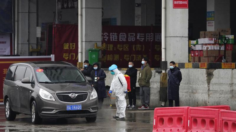 A worker in protective overall disinfects a vehicle from the World Health Organization convoy while they were visiting the Baishazhou wholesale market on the third day of field visit in Wuhan in central China's Hubei province on Sunday, Jan. 31, 2021. (AP)