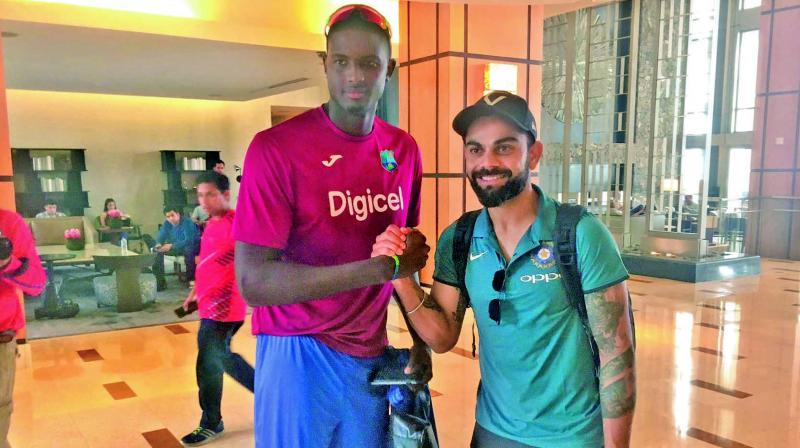 West Indies captain Jason Holder and his counterpart Virat Kohli pose on the India team's arrival in Port of Spain on Wednesday. Kohli & Co. will play five ODIs and a T20 in a series beginning Friday. (Photo: BCCI)