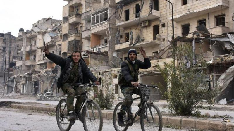 Syrian regime forces flash the victory sign in the former rebel-held Sukkari district in the northern city of Aleppo. Photo: AFP)